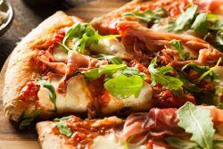 Pizza mit Rucola, Mozzarella und Parmaschinken